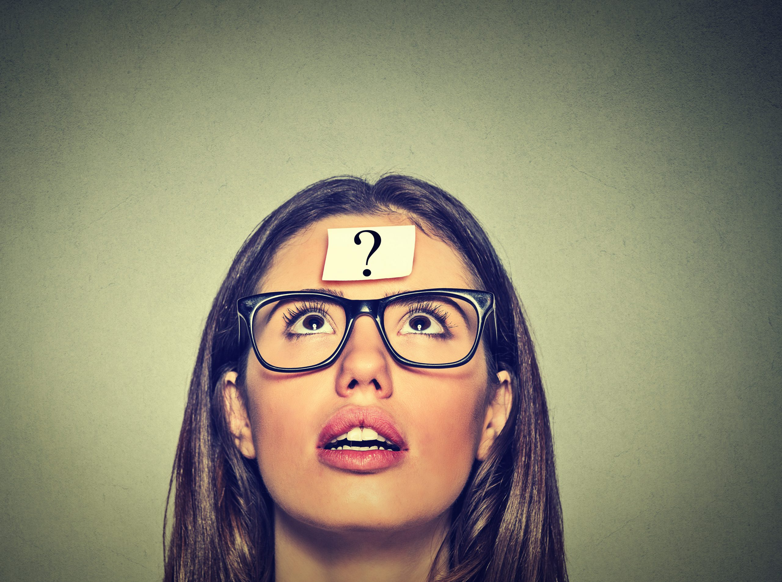 Denkende Frau mit offenem Mund und einem Fragezeichen auf der Stirn